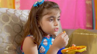 Slow motion shot of a little Indian girl eating fries in yellow plate