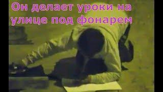 Мальчик делает уроки на улице, под фонарем потому, что у него дома нет света.