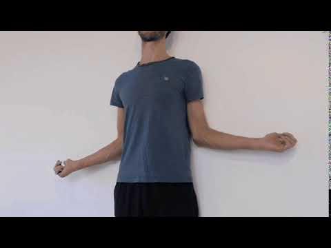 Renforcement des rotateurs externes de l'épaule debout contre un mur.