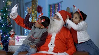 Young cheerful kids happily taking selfies with funny Santa Claus - Christmas time