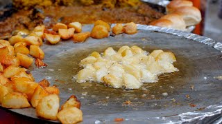 Potatoes being fried on a huge frying pan for chaat (Indian street food)