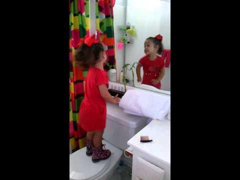 Niña cantando frente al espejo