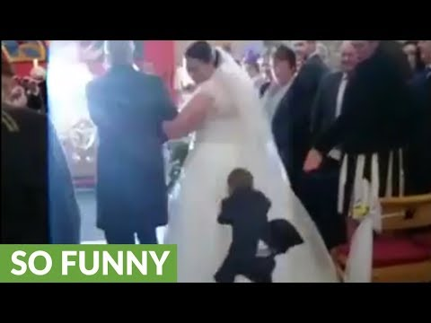 Kid dives onto bride's wedding dress while she walks down aisle