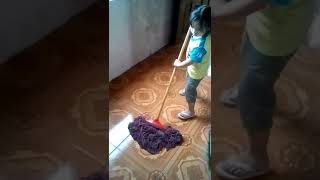 Little Girl cleaning the floor.