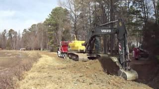 Excavator Loading a Quad Dump Truck