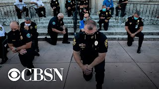 Police officers kneel and march in solidarity with protesters