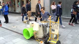 Guy plays drums on pots and plastic buckets