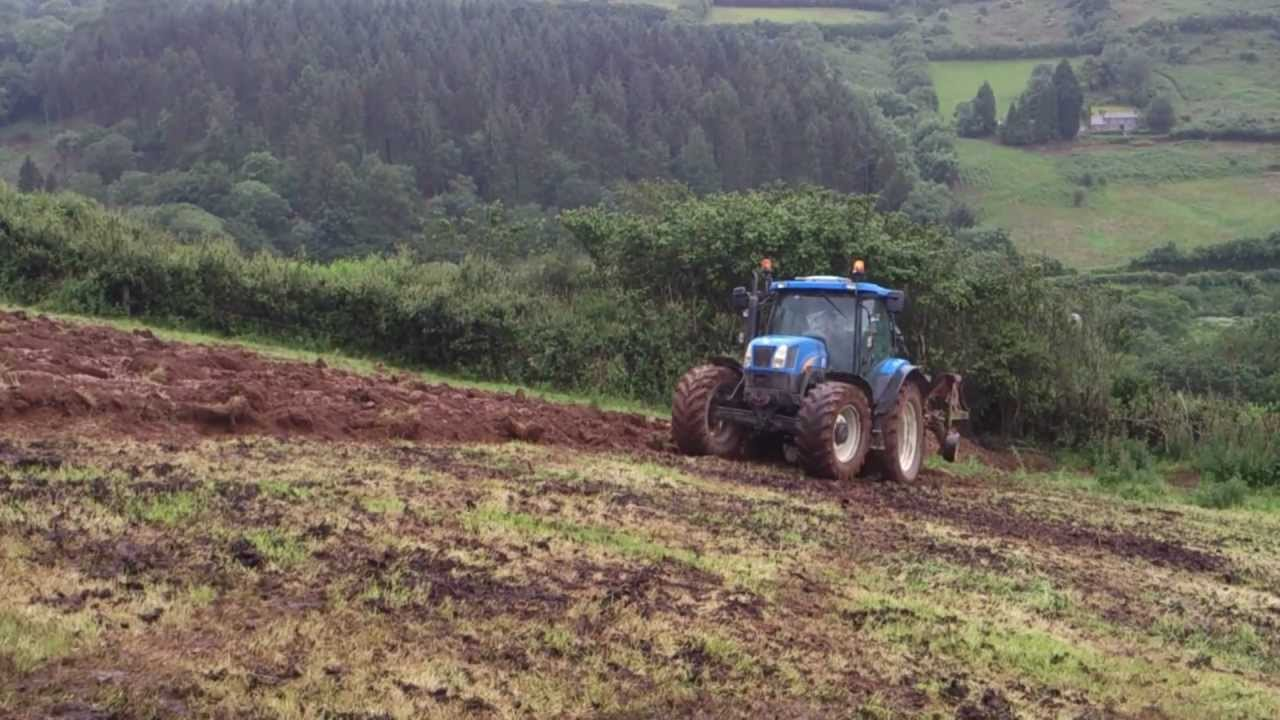 new holland ts115 ploughing up hill