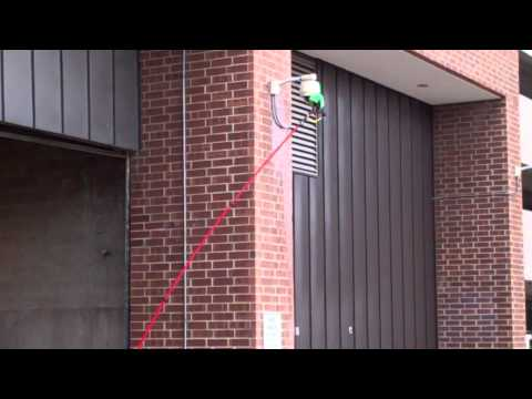 Cleaning a security camera with a water fed pole