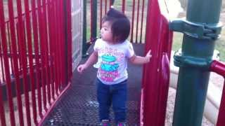 Toddler overcoming her fear of crossing playground bridge