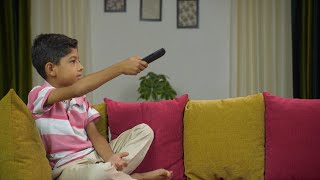 Young kid happily watching television at home during his summer vacations