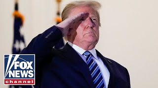 Trump salutes Marine 1 after arriving back at the White House