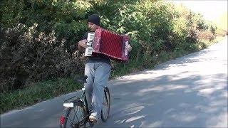 Tyłem na rowerze grając na akordeonie