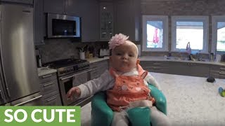 Baby enjoys ride atop robot vacuum cleaner
