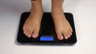 Indian female standing on a weight scale- Weight loss concept