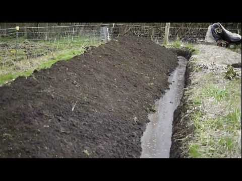 Hugelkultur Garden Swale creating south facing beds on a