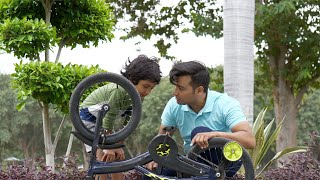 Attractive Indian father repairing his son's cycle on a summer day - leisure time