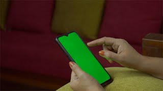 Woman hands using a smartphone with green mock-up screen - technology concept