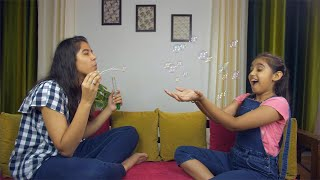 Pretty young children playing with soap bubbles at home - lifestyle kids concept