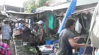 Train runs through Mae Klong Market in Thailand