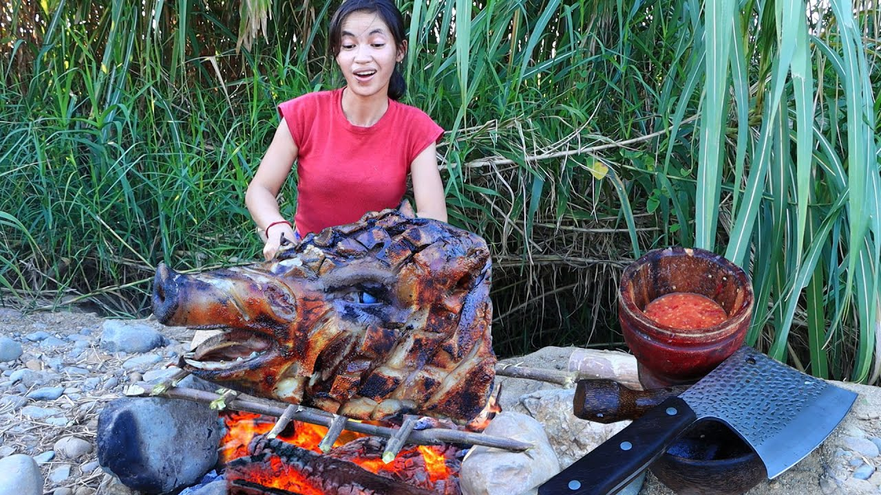 beautiful girl cooking head pig for eating - grilled head pig eating delicious