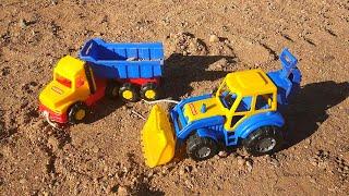 Синий трактор с прицепом и самосвал в песке