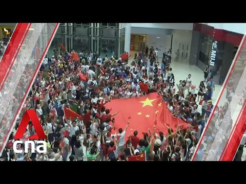 Hong Kong pro government protesters sing Chinese anthem in Kowloon mall