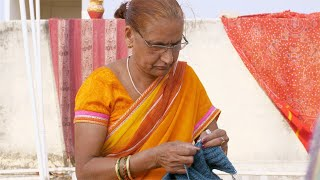 Stock video of a senior Indian woman knitting with wool yarn - Favorite hobby