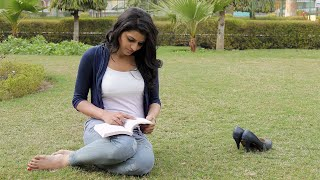 Girl sitting in a lawn and reading book