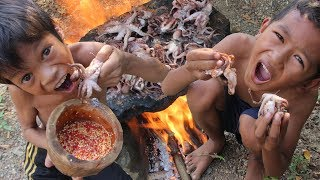 Boy cooking octopus on arock and eating