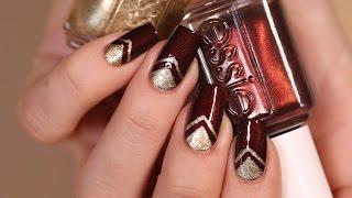 مناكير أحمر مميز مع المثلثات الذهبية
