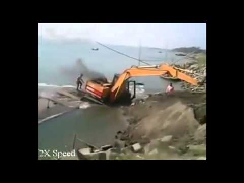 Workers sink boat loading digger