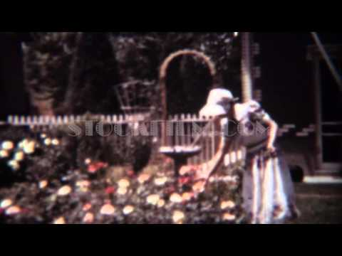1939: Woman gardening rose flowers front yard with white bonnet. DENVER, COLORADO