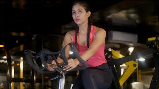 Focused young women / female working out on the exercise bike at the gym