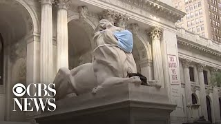 Lion statues outside New York Public Library wear face masks