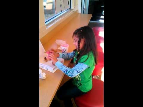 Pretty girl eats a doughnut at Krispy Kreme