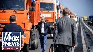 Putin rolls into Crimea on new bridge