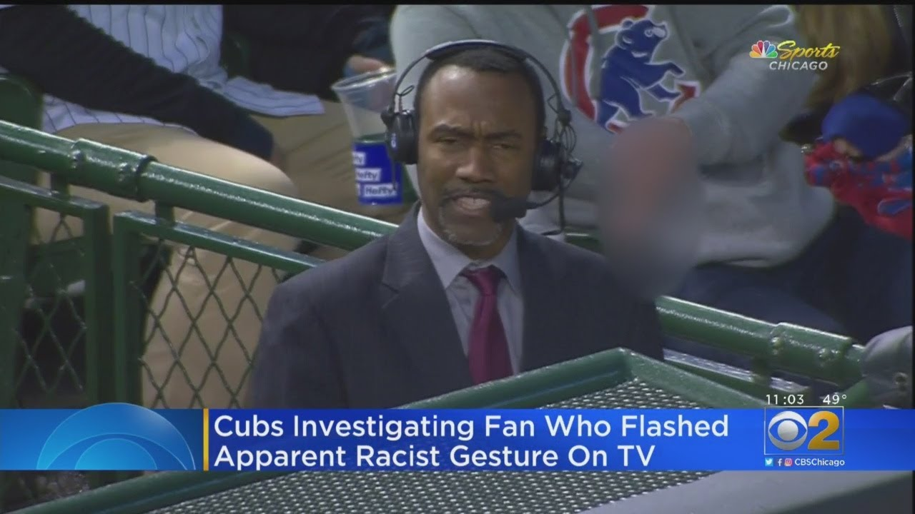 A Cubs fan's hand sign of stupidity, behind the black man