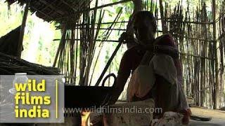 Aged Assamese lady roasting rice to make hando guri - Assam