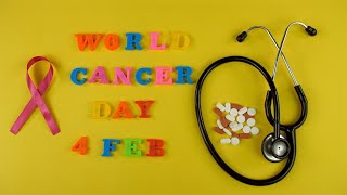 Woman hands spelling the words 'World Cancer Day 4 Feb' with colorful letters