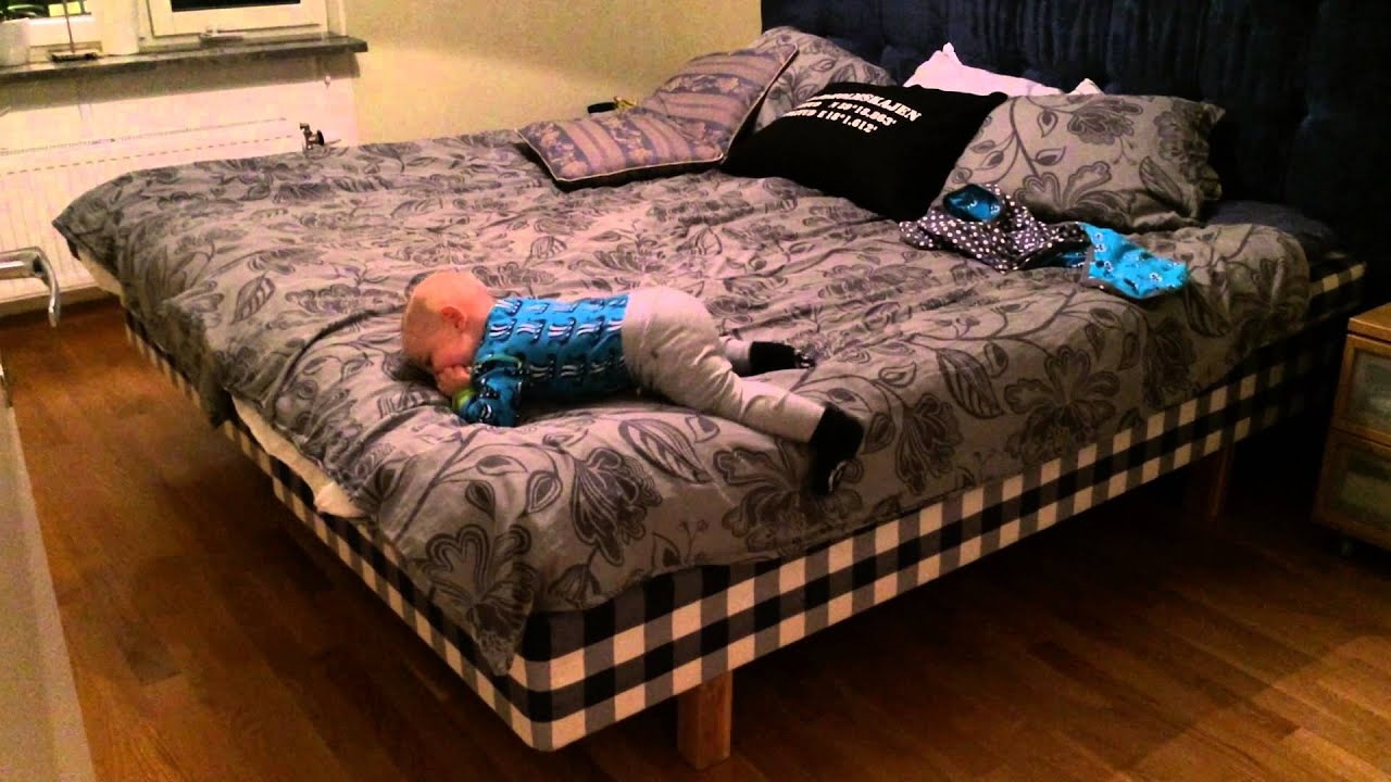 10 month old cute baby boy climbing out of bed on his own ...