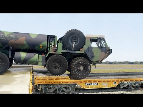 Loading Massive US Armored Trucks on Train during Heavy Rail Operation