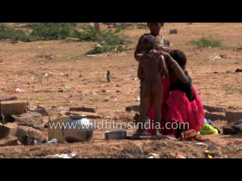 Rural Indian woman bathes her son in open area