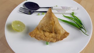 Fresh peas poured on a deep-fried crispy samosa in a ceramic white plate - Indian food