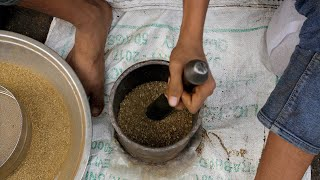 Slow motion of a man hand pounding raw spices in a stone mortar