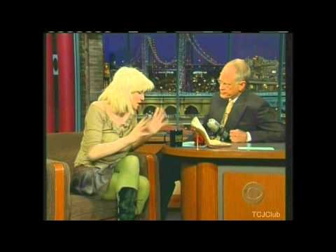 Courtney Love stands on Letterman's desk and pulls up her shirt on The Late Show